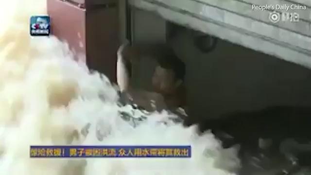 Người đàn ông được cư dân giải cứu bằng đoạn ống dẫn nước cứu hỏa.