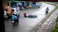 Cô gái gặp tai nạn vì vừa cầm dù vừa đi xe máy ở Thái Lan