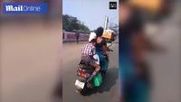 Cậu bé Ấn Độ vừa ngồi sau xe mẹ vừa thoăn thoắt làm bài tập về nhà