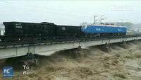 Hai đoàn tàu 7.000 tấn ngăn cầu bị lũ cuốn ở Trung Quốc