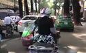 Người phụ nữ ngồi sau xe máy gánh theo lò than và nồi nước sôi cực kỳ nguy hiểm