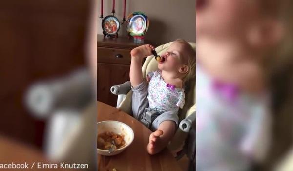 Bé gái không tay kiên trì xúc thức ăn bằng chân