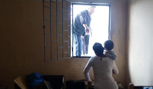 Cảnh người dân trèo qua cửa tum đi qua mái nhà xuống cầu thang máy
