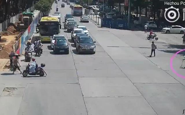 Người đàn ông lái xe máy chặn đầu hàng loạt ô tô để giúp bà cụ sang đường