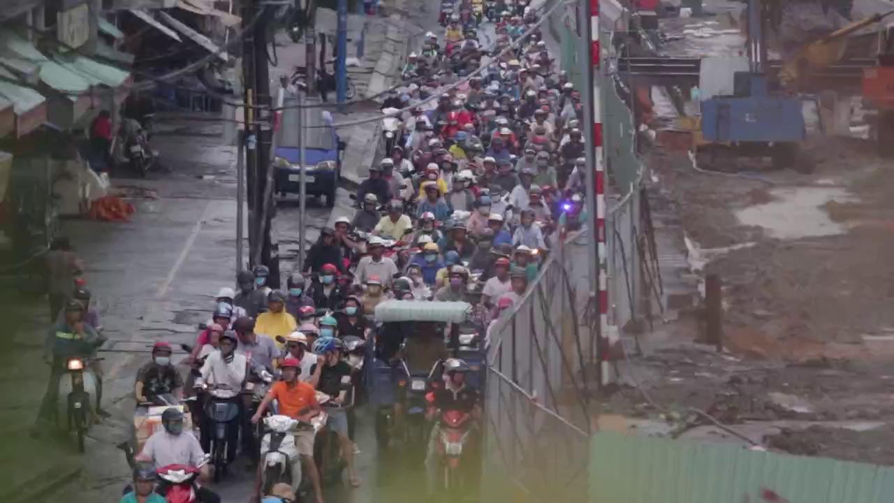 Trẻ em mệt mỏi cùng bố mẹ vượt mưa trở về thành phố