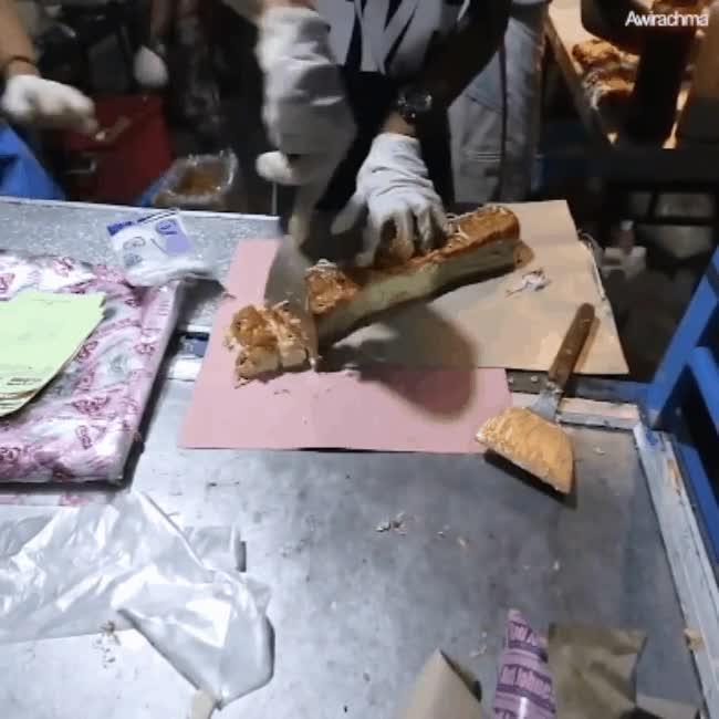 Người bán sẽ dùng dụng cụ cắt bánh ra thành từng khoanh nhỏ.