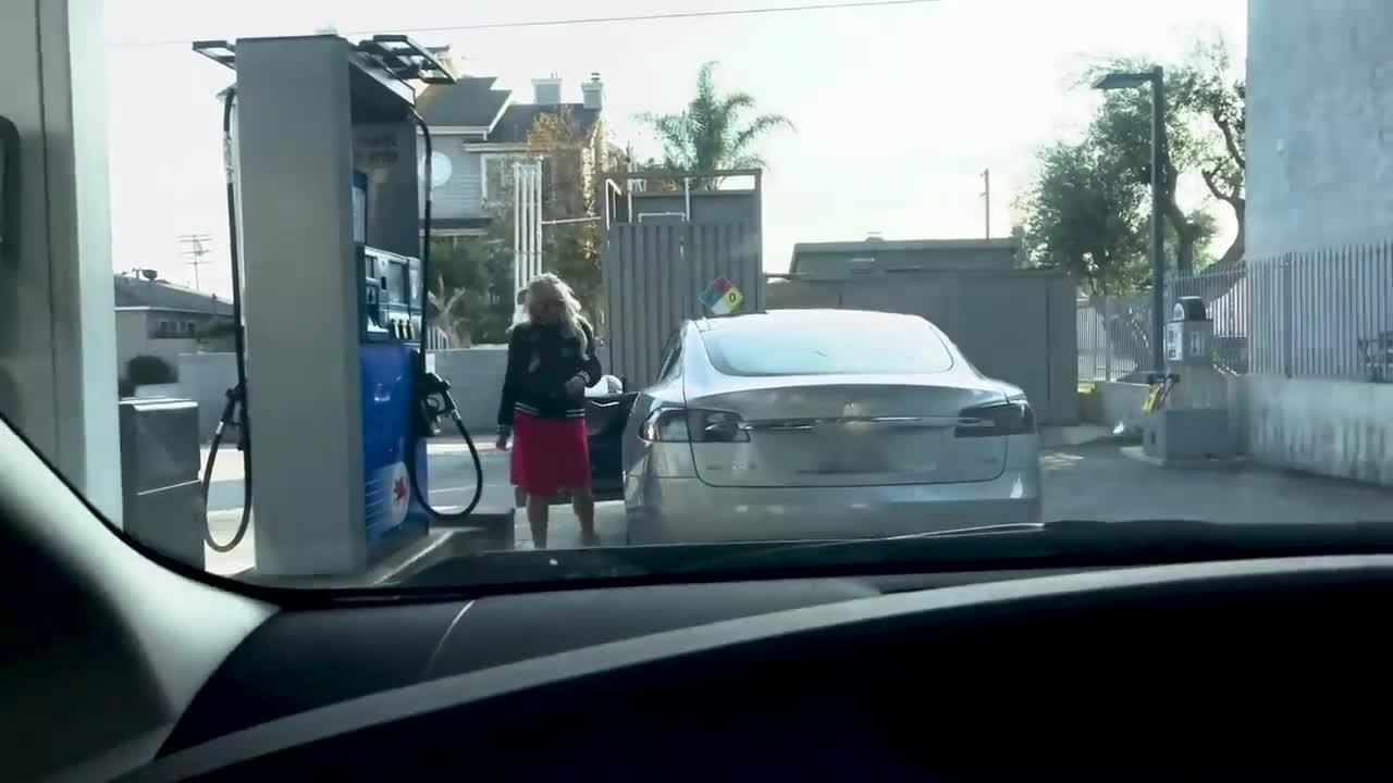 Chết cười với chị gái tóc vàng hoe đỏ mắt tìm cách... đổ xăng cho xe Tesla Model S.
