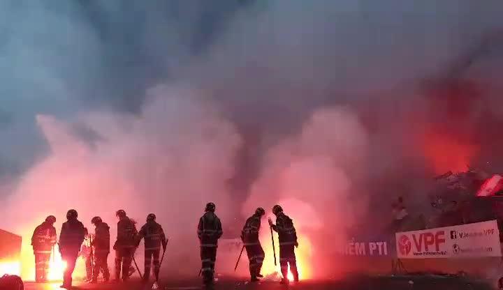 Lực lượng cứu hỏa phải vào cuộc để dập tắt các quả pháo sáng được ném xuống sân