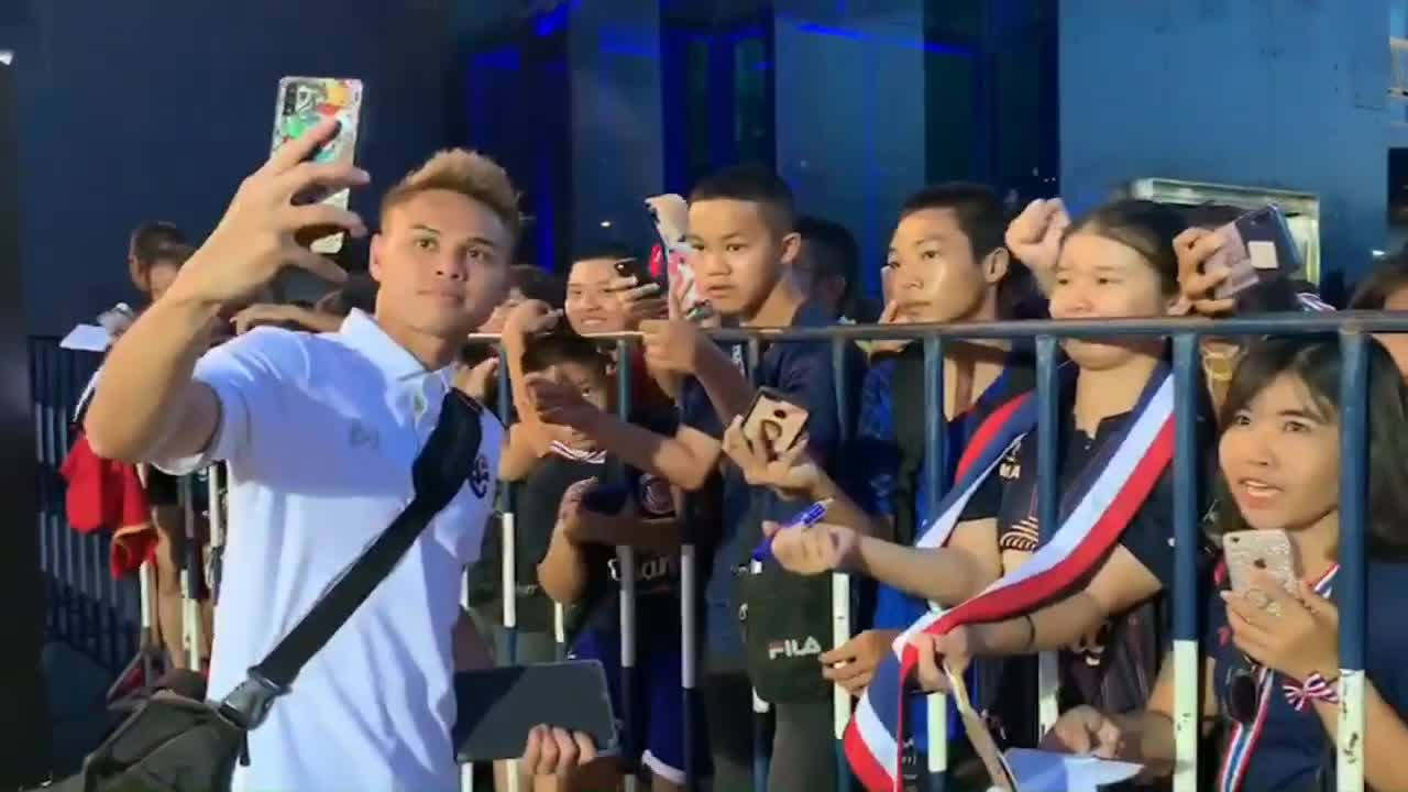 Theerathon Bunmathan và đồng đội đi dọc hàng rào để tặng chữ ký, chụp ảnh selfie với người hâm mộ trước khi lên xe về khách sạn.