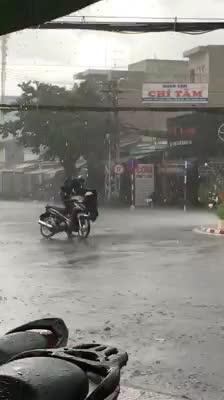 Mưa như trút, nước, cha đứng mặc áo mưa cho con nhưng hành động này khiến dân mạng tranh cãi