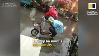 Cảm động hình ảnh cậu bé lấy thân che yên xe cho mẹ giữa trời mưa